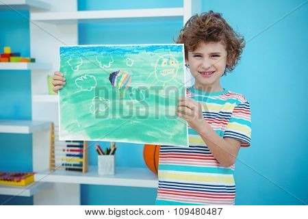 Smiling boy holding a picture beside a shelf