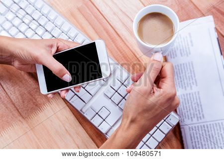 Businesswoman holding hot beverage and smartphone on desk
