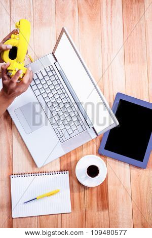 Overhead of feminine hands holding headphones with stuff on desk
