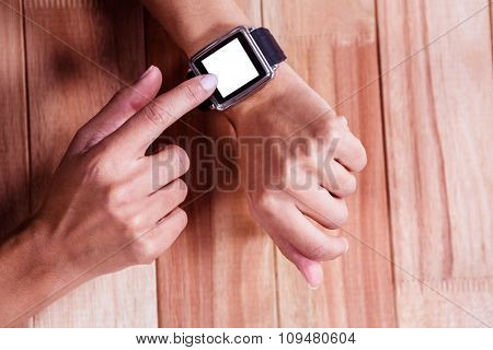 Part of hands typing on a watch on wooden desk