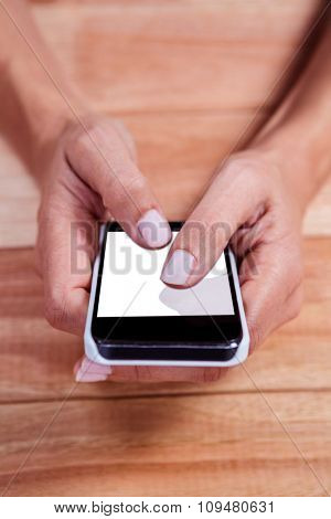 Part of hands typing on smartphone on wooden desk