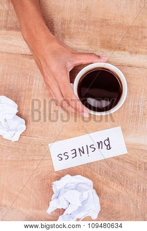 Above view of paper ball and coffee on wooden desk