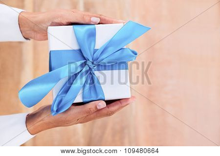 Woman presenting gift with blue ribbon on desk