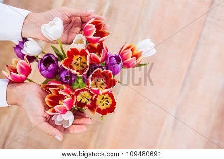 Woman holding a bouquet of flower on wood desk