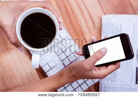 Businesswoman using her smartphone on desk at work