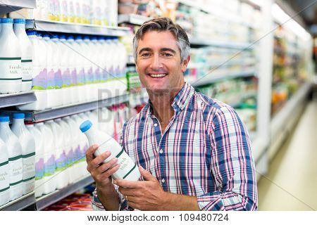 Smiling man holding milk bottle in the supermarket