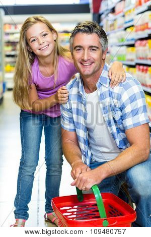 Father and daughter at the supermarket smiling at the camera