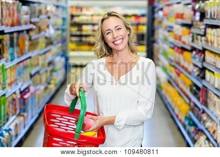 Woman buying food in supermarket and smiling at the camera