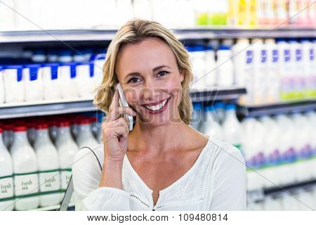 Smiling blonde woman having a call phone at the supermarket