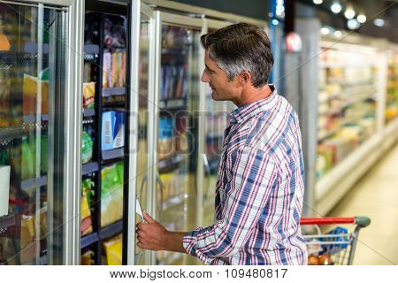 Side view of man opening supermarket fridge
