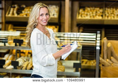 Blonde woman standing and checking list smiling at the camera