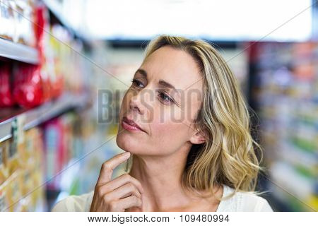 Thoughtful woman looking at shelves in the supermarket