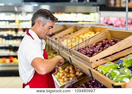 Seller filling vegetables box at supermarket