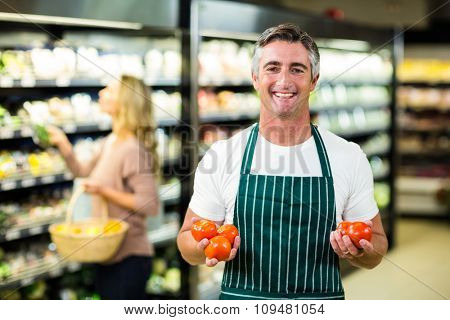 Smiling worker holding vegetables at supermarket