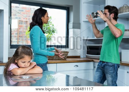 Sad child listening to parents argument in the kitchen