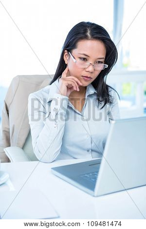 Serious businesswoman using laptop at the desk in work