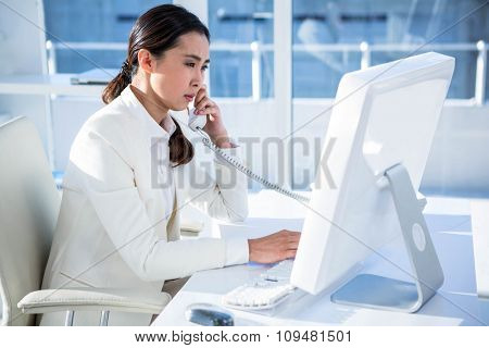Smiling businesswoman using computer and telephone at the desk in work