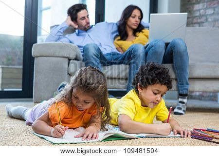 Children laying on the carpet drawing in living room while parents on sofa using laptop
