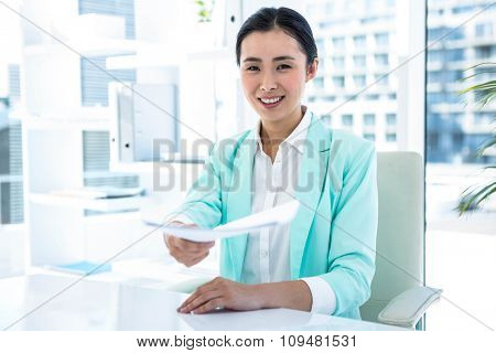 Smiling businesswoman taking notes at the desk in work