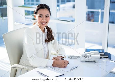 Smiling businesswoman taking down notes at the desk in work
