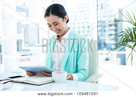 Businesswoman using her tablet pc at the desk in work