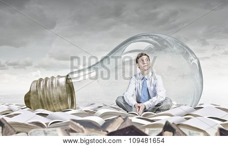 Young thoughtful businessman trapped inside of light bulb