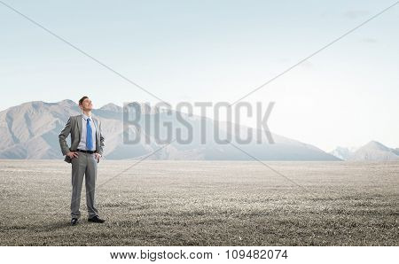 Young confident businessman with arms on waist outdoor