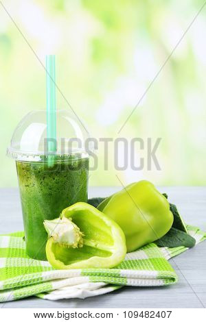 Fresh vegetable juice on color wooden table, on bright background