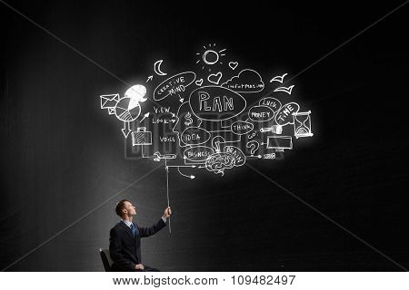 Businessman in chair holding sketched plan strategy on rope