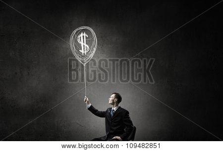 Businessman in chair holding dollar sign balloon