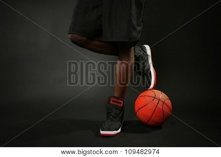 African American basketball player with ball on dark background