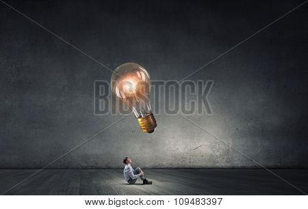 Young businessman sitting on floor and looking up on glowing bulb
