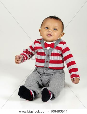 A handsome young baby sitting in his striped sweater and bow tie.  On a gray background.
