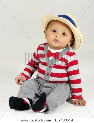 An adorable baby born sitting in his red and gray striped sweater, red bow tie and fedora.  On a gray background.