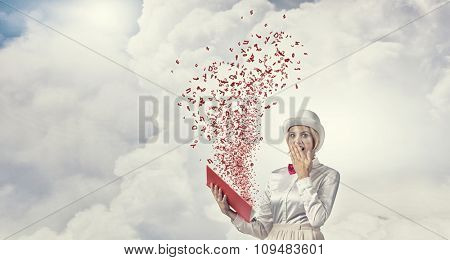 Young woman in white hat with opened book in hands and characters flying out
