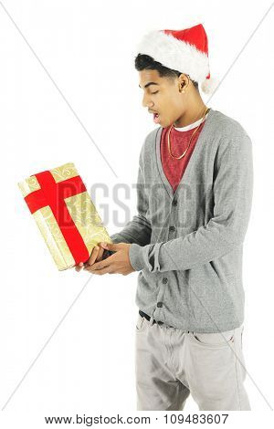 A tall teen boy surprised to receive a gift.  He's wearing a Santa hat.  On a white background.