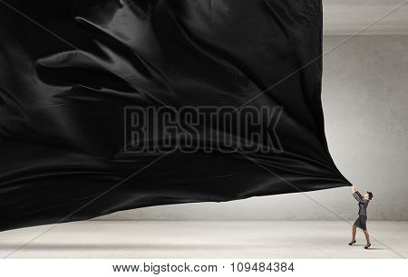 Young businesswoman in suit and bowler hat pulling curtain
