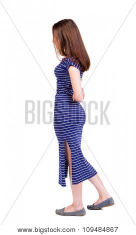 back view of standing young beautiful  woman.  girl  watching. .  Isolated over white background. Girl in a blue striped dress stands sideways hiding his hands behind his back.