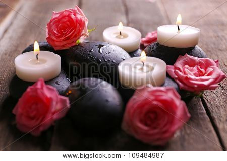 Tenderness relaxing composition with pebbles, roses and candles on wooden background, close up