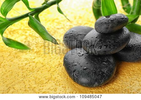 Spa stones and bamboo branch on a light background