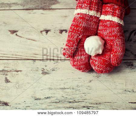 Mitten with snowball on wood floor. Winter decoration