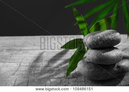 Spa stones and green flower, on dark grey background