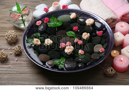 Spa composition of candles, flowers and stones in water, on wooden background