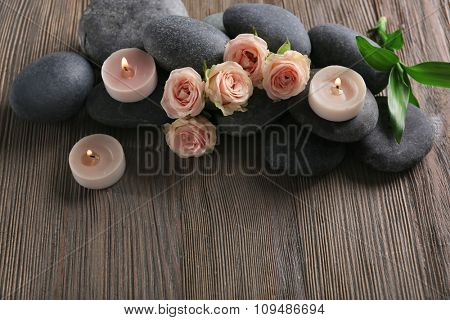Spa composition of candles, flowers and stones on brown wooden background