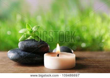 Spa stones and candle on wooden table closeup