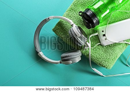 Headphones and sport equipment on blue background