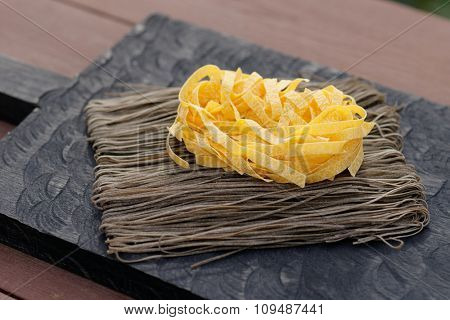 Two types of pasta on wooden plank, sunlight