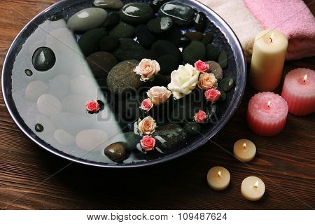 Spa composition of flowers and stones in water on wooden background