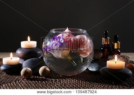 Beautiful spa composition on wicker napkin on dark background