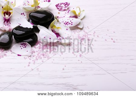 Orchid and zen stones on wooden background close-up